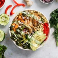 honey ginger chicken power bowl with veggies, freekeh and lettuce greens packed in a bowl and topped with creamy lime dressing