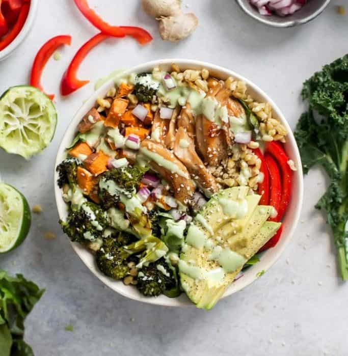 honey ginger chicken with avocado, roasted broccoli, sweet potato, red bell pepper, red onion, freekeh and lettuce greens packed in a bowl and topped with creamy lime dressing