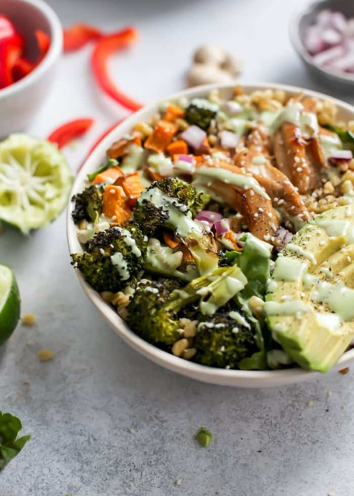 honey ginger chicken power bowl with roasted broccoli, avocado, sesame seeds, sweet potatoes, freekeh, red bell pepper and lettuce greens