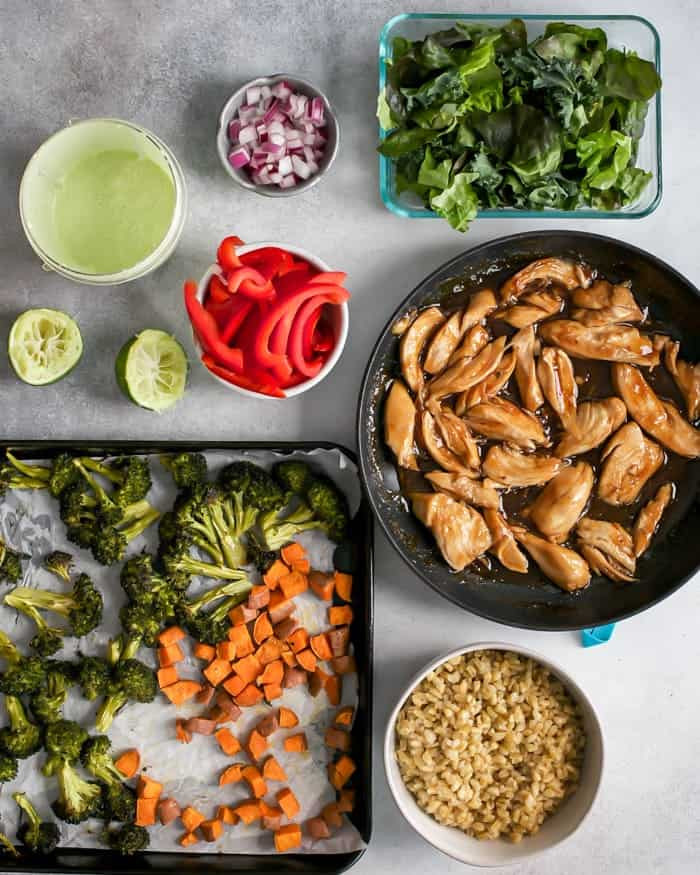 pan of roasted broccoli and sweet potatoes, bowl of freekeh, container of lettuce, sliced red bell pepper, diced red onion, limes, pan of honey ginger chicken