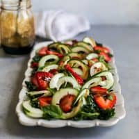 strawberry kale salad with spiralized cucumber and balsamic reduction on white serving platter