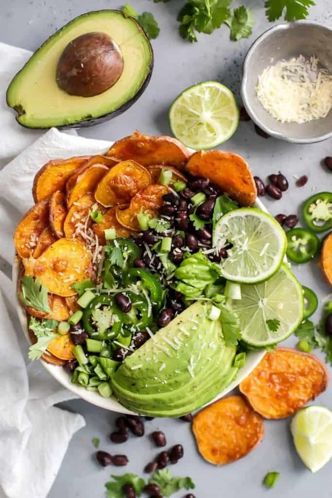 Loaded Sweet Potato Nacho Salad Bowls with black beans, avocado, lime, parmesan, cilantro, jalapeno