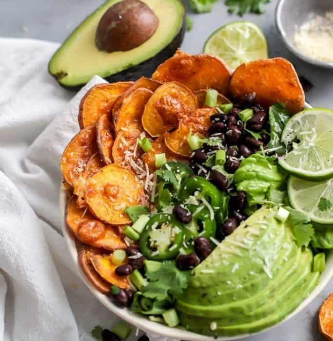 loaded sweet potato nacho salad bowl with avocado, black beans, jalapeno and lime