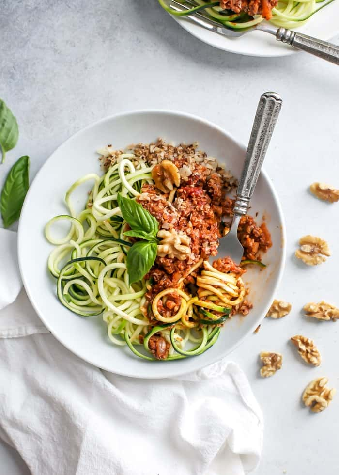 bowl of meatless walnut bolognese over zucchini noodles with fork and fresh basil