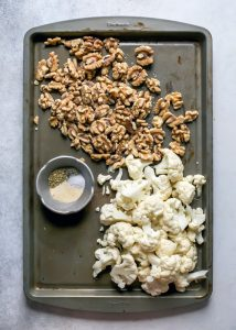 walnuts and cauliflower on pan with spices in pinch dish