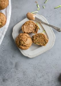 healthy zucchini muffins cut in half with almond butter, served on small off white plate
