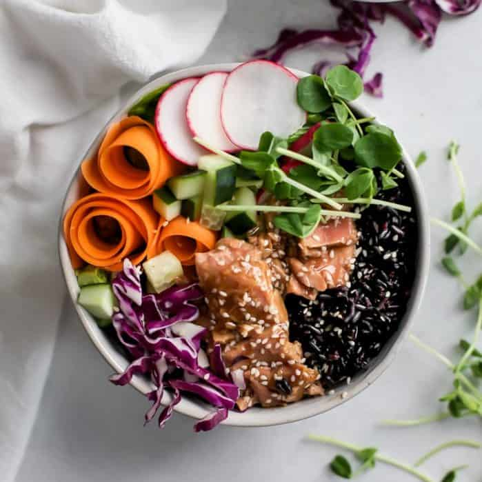 bowl of ahi tuna covered with black rice, carrot ribbons, purple cabbage, radishes and sprouts