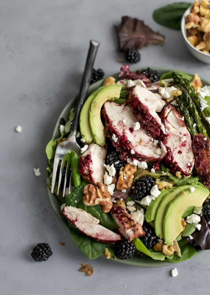 grilled blackberry balsamic chicken on plate of salad greens with feta, asparagus, avocado and balsamic dressing
