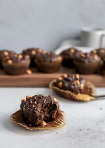 bite out of chocolate peanut butter muffin with chocolate muffins on wooden board