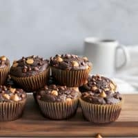 chocolate peanut butter muffins on wooden board with coffee mug behind