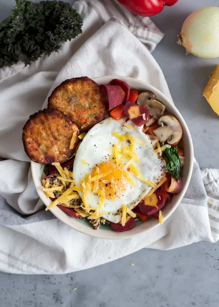 bowl of quinoa, kale, veggies, fried egg with cheese and hash browns