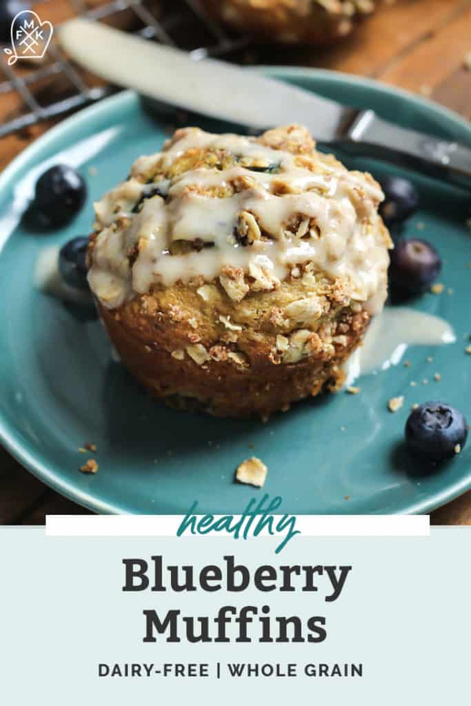 healthy blueberry muffin on small blue plate surrounded by blueberries