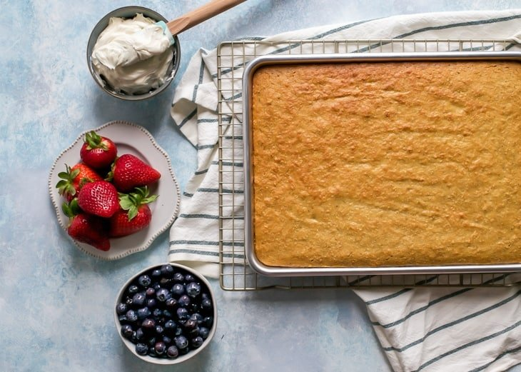sheet cake in quarter sheet pan for paleo flag cake. berries and frosting in bowls