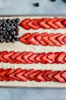 flag cake in quarter sheet pan with blueberries and strawberries