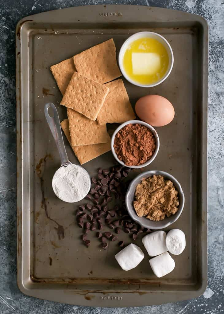 graham crackers, flour, cocoa powder, sugar, butter, egg, chocolate chips and marshmallows for s'mores brownie skillet