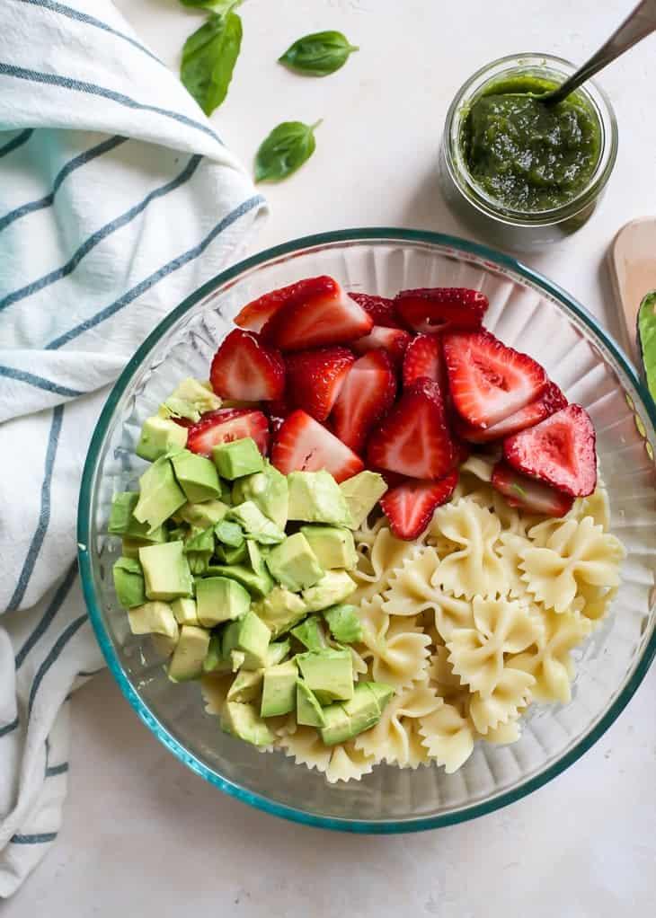 ingredients for pesto pasta salad in glass bowl