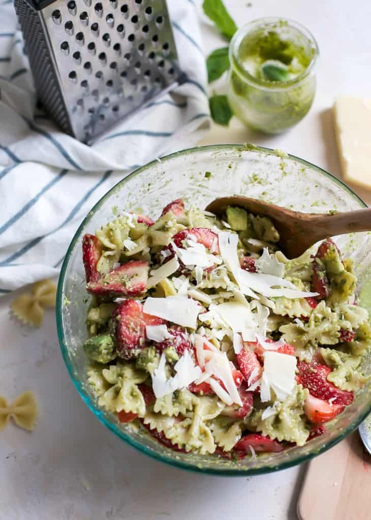 pesto pasta salad with strawberries and shaved parmesan in bowl