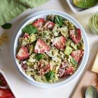 pesto pasta salad with strawberries in white bowl