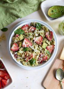 pesto pasta salad with strawberries in white bowl