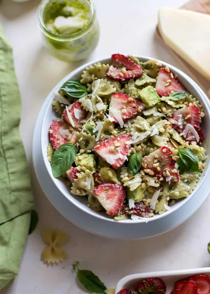 pesto pasta salad with strawberries and avocado in white bowl