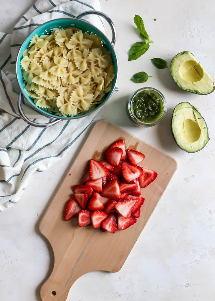sliced strawberries on cutting board, bowtie pasta in colander, halved avocado, pesto in jar