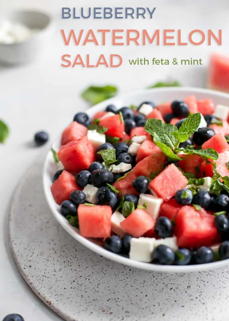 watermelon salad in white bowl tossed with blueberries, feta and mint