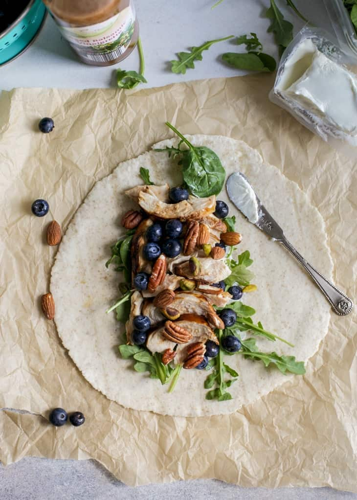 balsamic chicken wrap with blueberries and goat cheese laid on flat on parchment paper