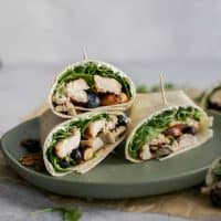 stacked balsamic chicken wraps on green plate with blueberries and goat cheese