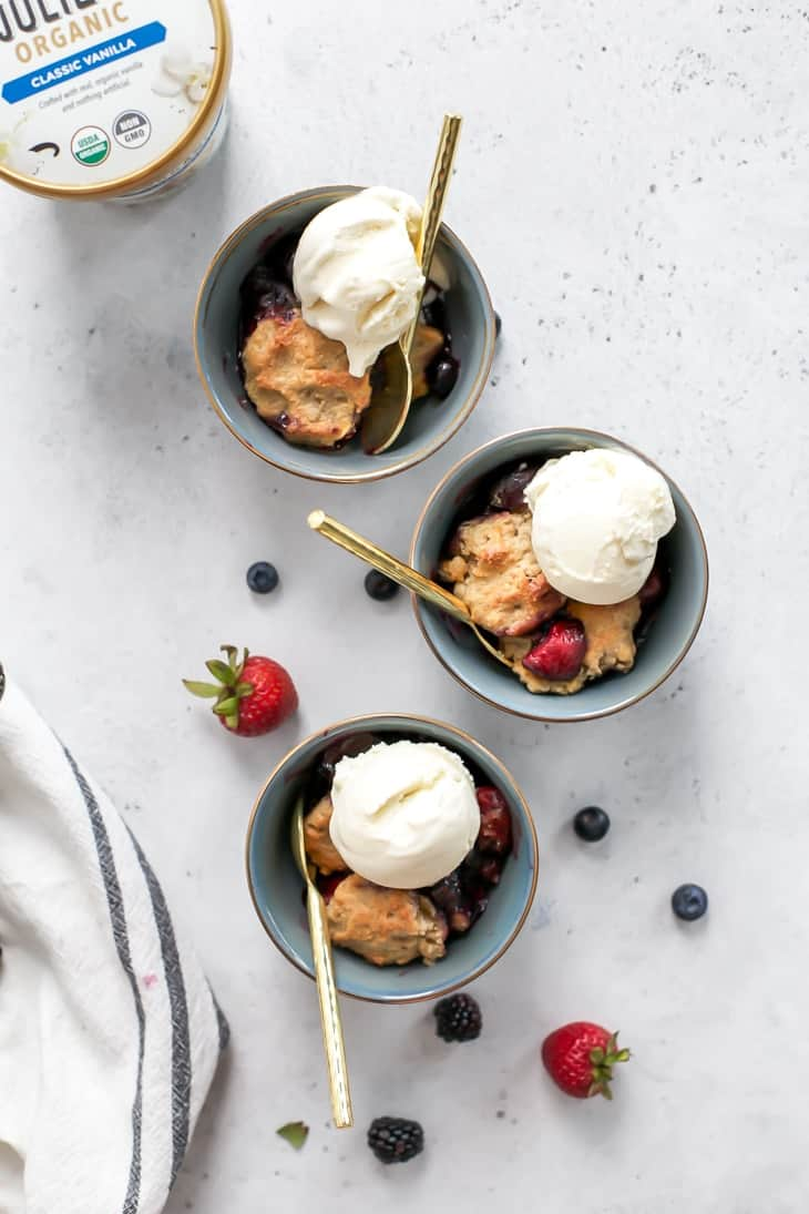three gold rimmed bowls with gold spoons and cherry berry cobbler dessert
