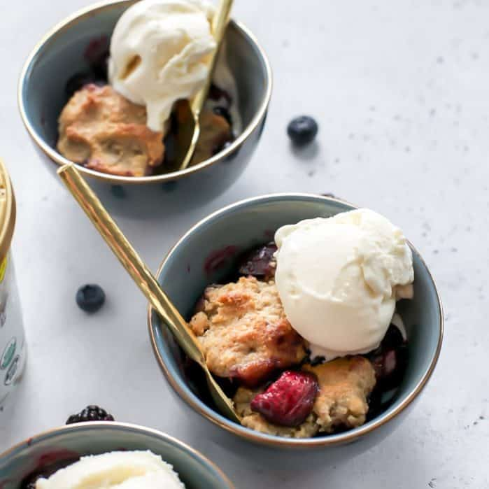 bowls of berry cobbler with ice cream and gold spoons