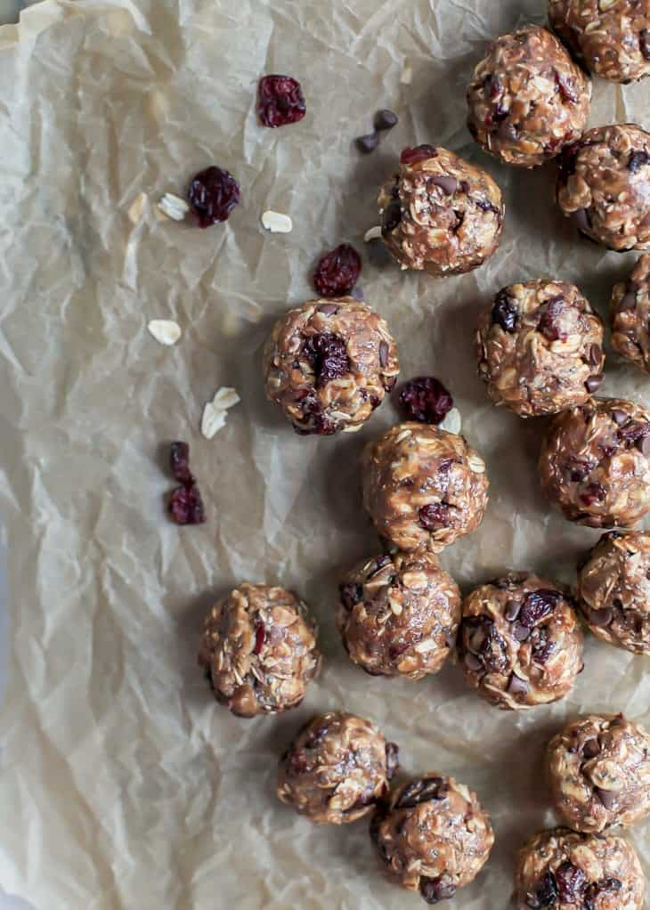 cherry chocolate chip energy balls with oats on brown parchment paper