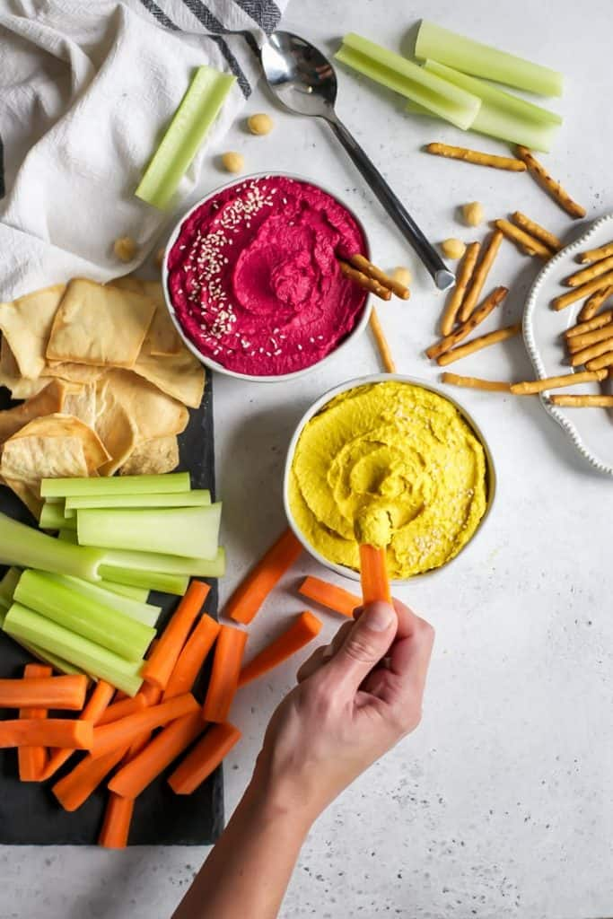 bowls of beet hummus with hand dipping carrot into hummus