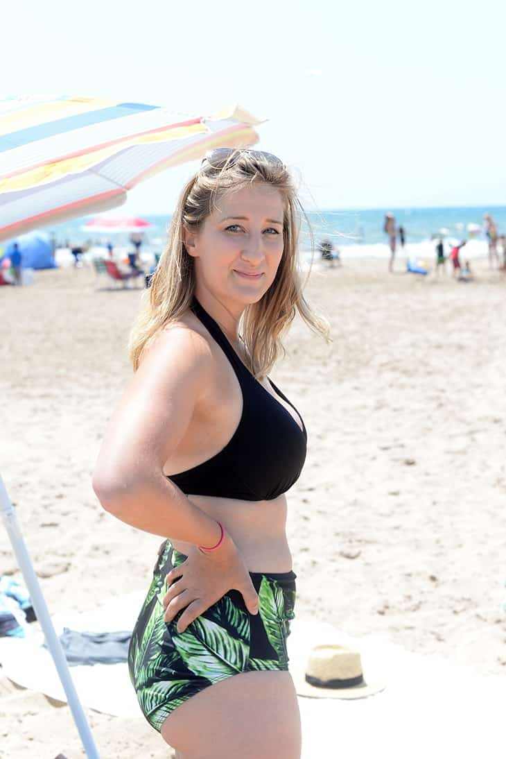 On the beach in black halter top and albion fit laguna high waist bottoms for swimsuit season