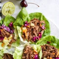 Chipotle Cherry BBQ Pulled Pork Lettuce Wraps on platter with lime and avocado