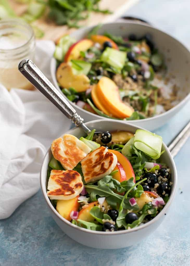 fried halloumi on salad with peaches blueberries and arugula in bowl
