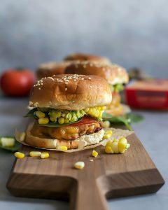 cheddar turkey burger with corn on wooden board