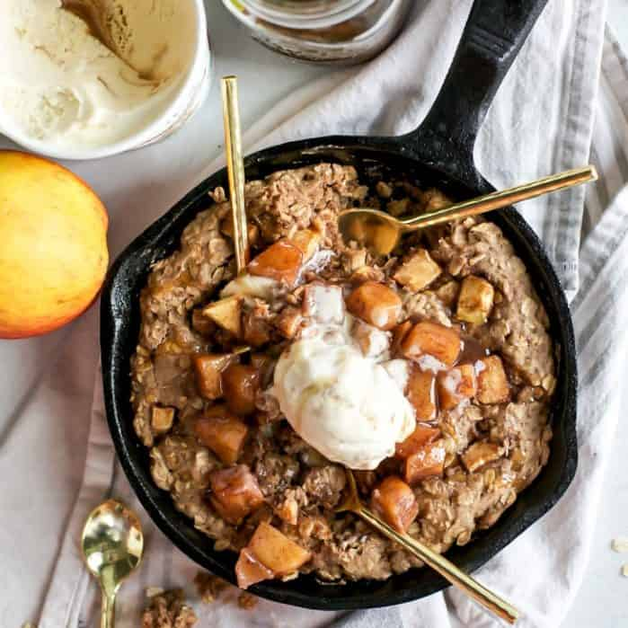 apple cookie skillet topped with cooked apples and ice cream with gold spoons