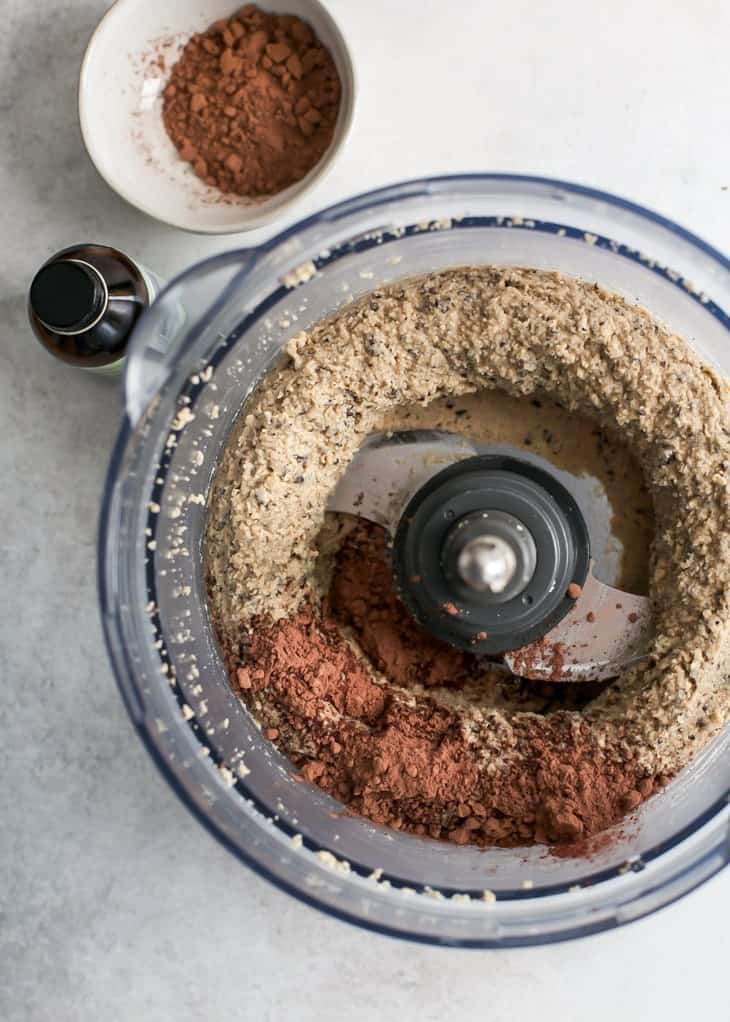 Food processor bowl with ground cashews, espresso beans and cacao powder.
