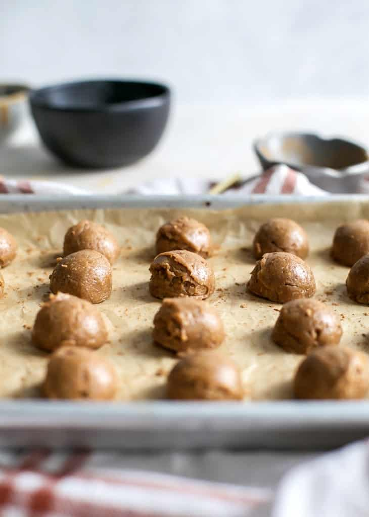 peanut butter cookie dough bites on lined baking sheet