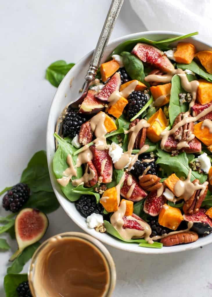 bowl of blackberry fig salad with roasted sweet potatoes and tahini dressing in jar