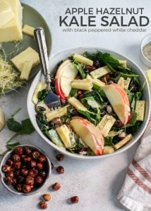 kale salad bowl with apples, hazelnuts and white cheddar
