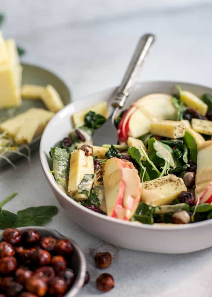 Fork in bowl with white cheddar cheese on apple hazelnut kale salad