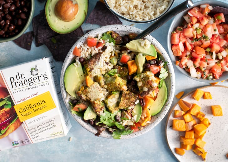California veggie burger burrito bowl with sweet potatoes and avocado on wooden board