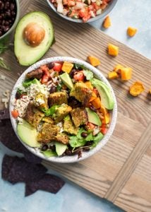 veggie burger burrito bowl with sweet potatoes and avocado on wooden board