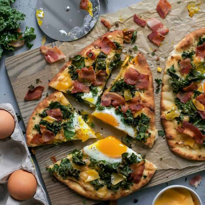 Cracked egg on naan breakfast pizza with cheddar, kale and bacon