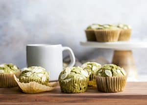 matcha muffins on wooden board with coffee mug and cake stand