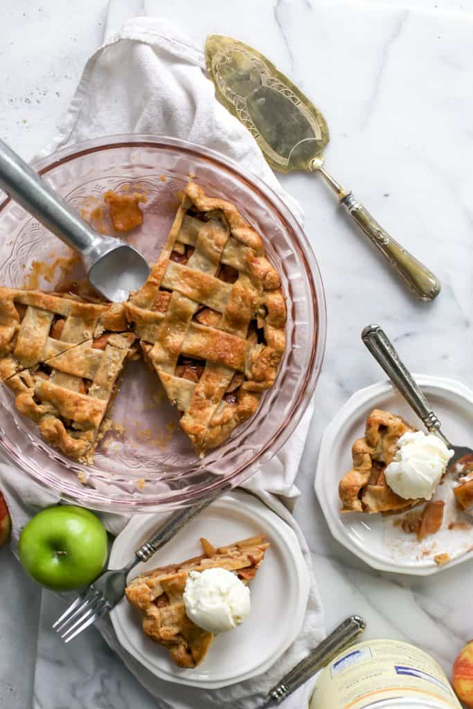 apple pie plates with ice cream next to pan of pie