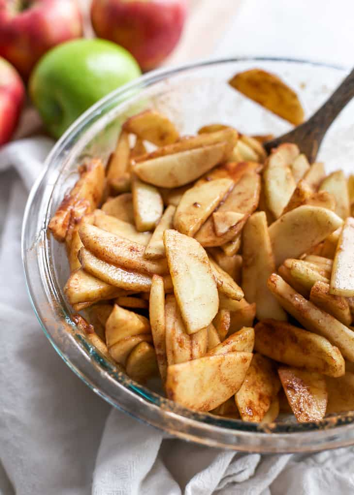 bowl of apples in cinnamon and sugar for apple pie
