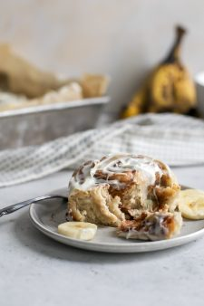 banana cinnamon roll on plate with fresh banana slices