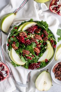 bowl of pear salad with fresh pomegranates and candied pecans